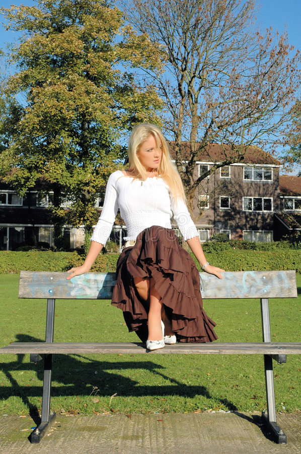 Ona a bench. Young beautiful woman on a bench in the park royalty free stock photos