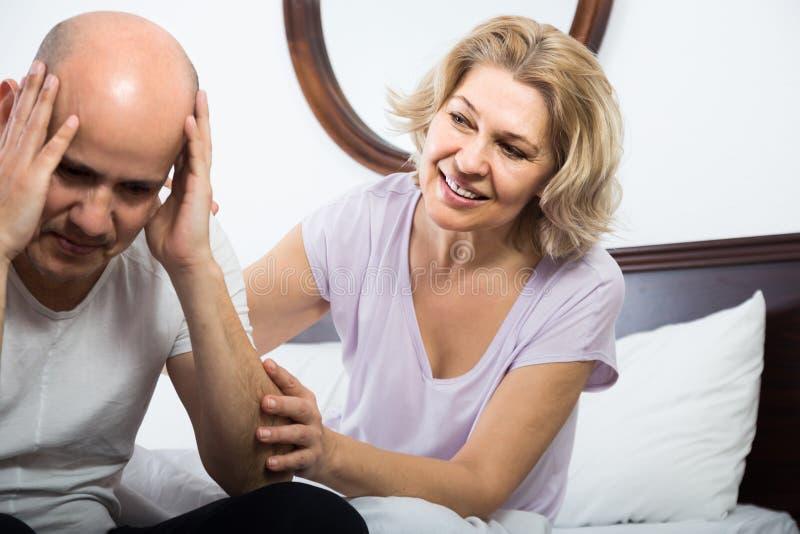 Żona miły pociesza wzburzony mąż w sypialni obrazy stock