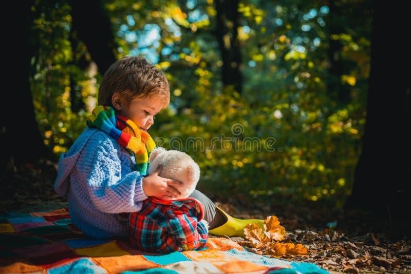 Onafscheidelijk met stuk speelgoed Spel van het jongens het leuke kind met teddybeerstuk speelgoed bosachtergrond Het kind nam fa royalty-vrije stock foto