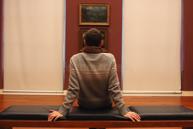 Onbekende mensenzitting met zijn rug op bank en het bekijken het schilderen van beeld in Art Museum, Europa royalty-vrije stock fotografie
