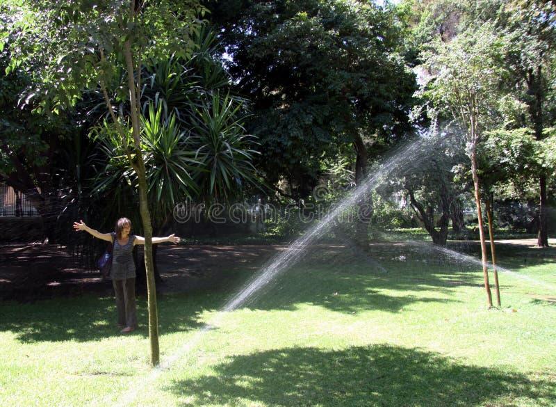 Onbekende vrouw onder de nevel van fonteinen in Maria Luisa Park in Sevilla royalty-vrije stock fotografie