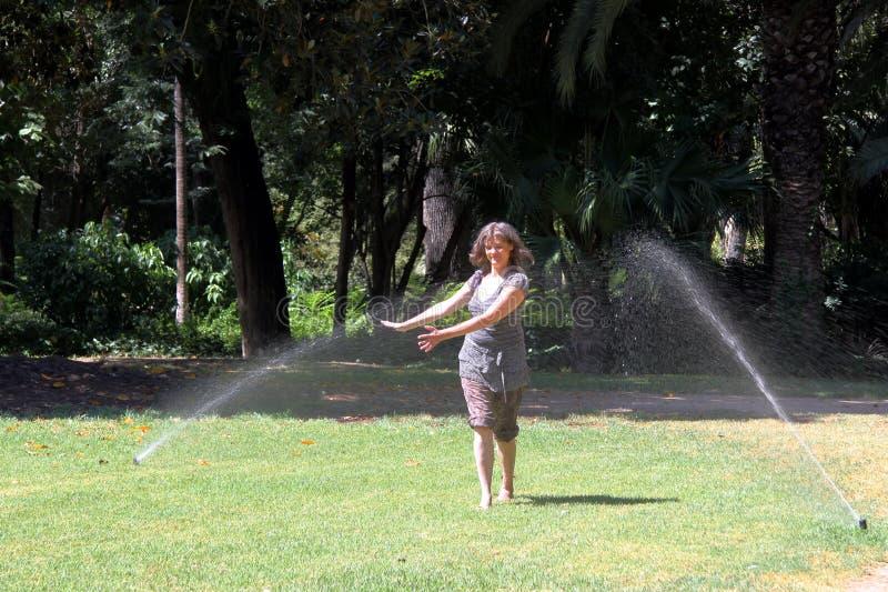 Onbekende vrouw onder de nevel van fonteinen in Maria Luisa Park in Sevilla stock foto