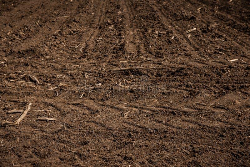 Onbewerkt land, gebied met wielsporen in de lente Vuiltextuur De textuur van het het vuilgebied van het land royalty-vrije stock fotografie