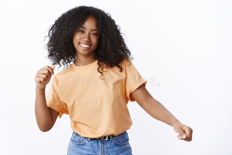 Onbezorgd aantrekkelijk gelukkig jong Afrikaans-Amerikaans krullend-haired meisje dat dansende golvende handen van de de lente de stock fotografie