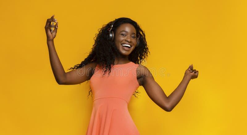 Onbezorgd Afrikaans Amerikaans meisje die en aan muziek dansen luisteren royalty-vrije stock afbeelding