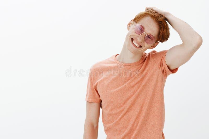 Onbezorgd knap roodharige Europees mannetje met sproeten, overhellend hoofd en krassend haar terwijl het glimlachen van vreugdevo royalty-vrije stock afbeeldingen