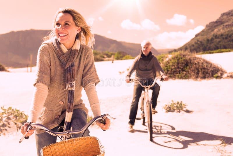 Onbezorgd paar die op een fietsrit gaan op het strand stock illustratie