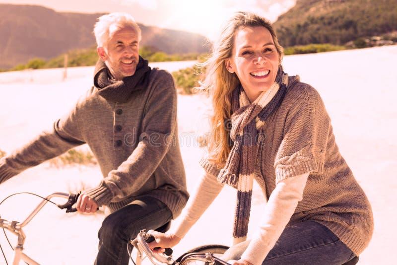 Onbezorgd paar die op een fietsrit gaan op het strand vector illustratie