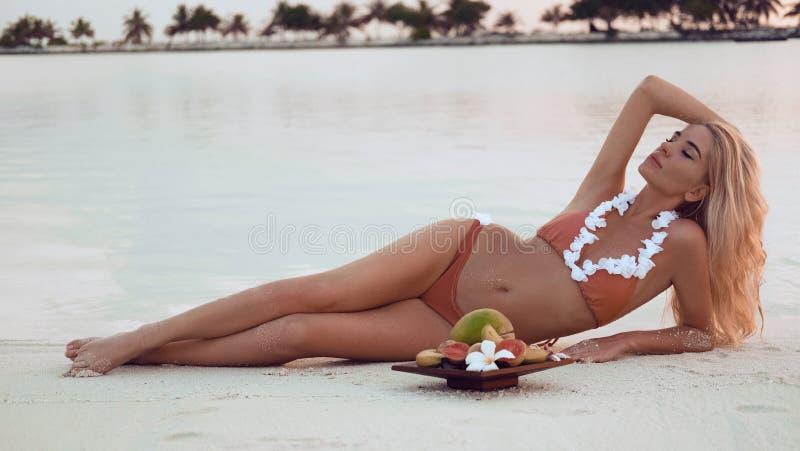Onbezorgde blondevrouw die op wit zand liggen die van Mooie Zonsondergang op Tropisch Strand genieten Sexy bikinimodel met exotis stock afbeelding