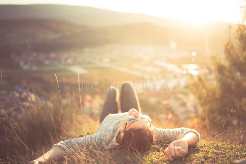 Onbezorgde gelukkige vrouw die op groene grasweide liggen bovenop de klip die van de bergrand van zon op haar gezicht genieten He stock afbeeldingen