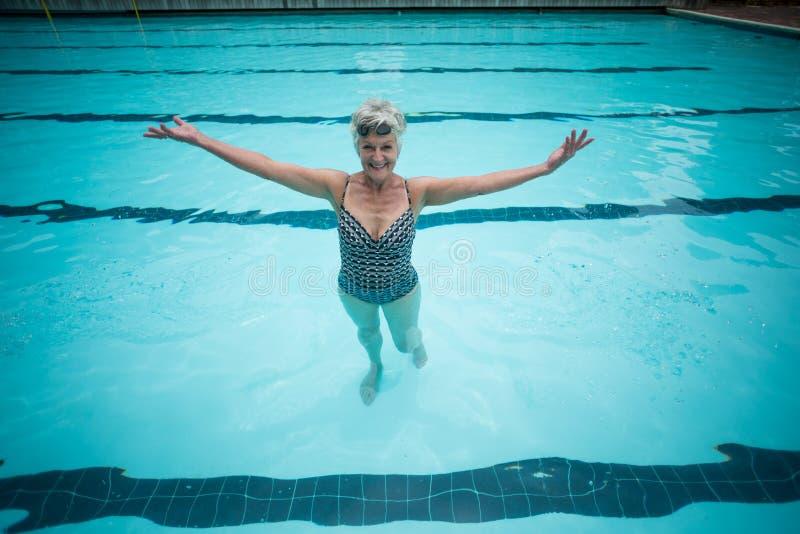 Onbezorgde hogere vrouw die in pool zwemmen stock afbeeldingen