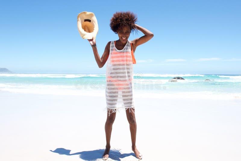 Onbezorgde jonge Afrikaanse vrouw met hoed die zich op strand bevinden royalty-vrije stock afbeelding
