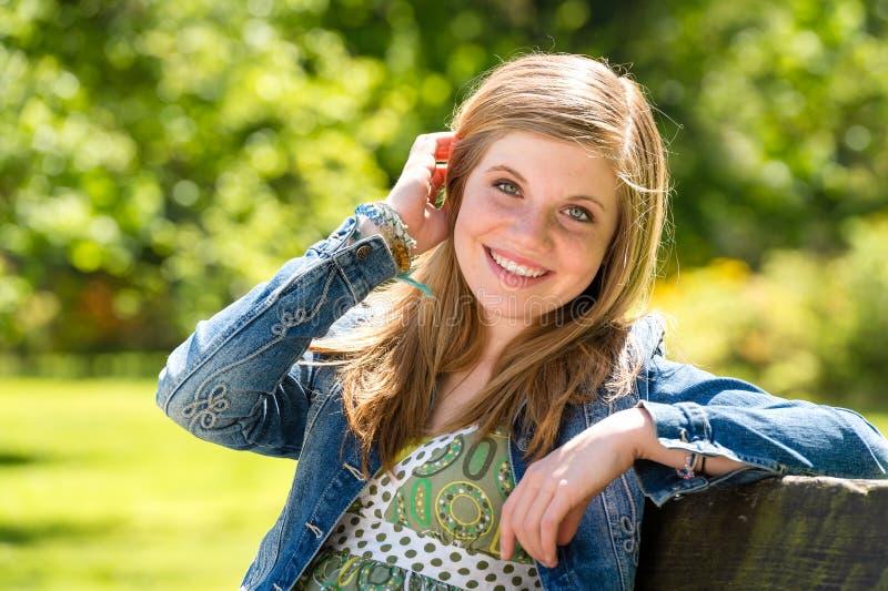 Onbezorgde jonge vrouw die van zonneschijn buiten genieten royalty-vrije stock foto