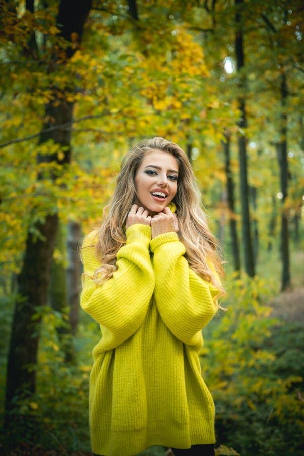 Onbezorgde jonge vrouw in in uitstekende rode trui of sweater Gelukkige jonge vrouw in park op zonnige de herfstdag De herfst royalty-vrije stock afbeelding