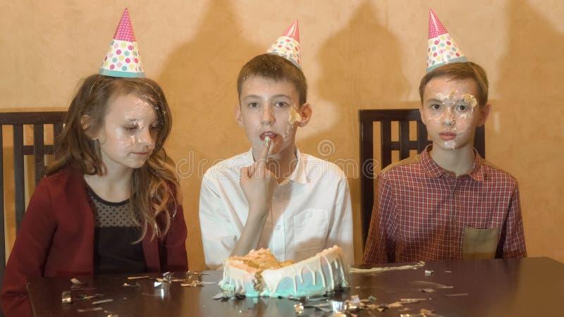 Onbezorgde kinderen bij een verjaardagspartij gezicht van jong geitje ` s in de cake en het glimlachen stock foto's