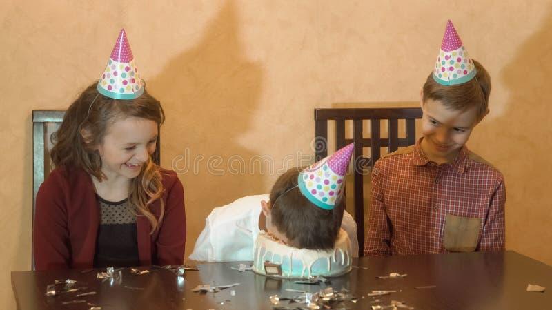 Onbezorgde kinderen bij een verjaardagspartij jongen ondergedompeld gezicht in de verjaardagscake Het concept van de familievieri royalty-vrije stock fotografie