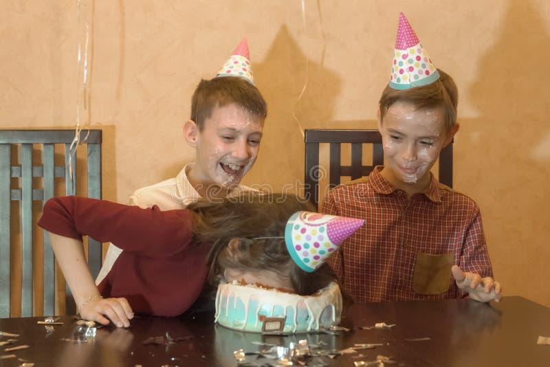 Onbezorgde kinderen bij een verjaardagspartij meisje ondergedompeld gezicht in de verjaardagscake stock foto