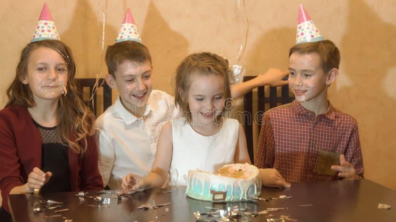 Onbezorgde kinderen bij een verjaardagspartij ziet het vrienden ondergedompelde feestvarken in de verjaardagscake onder ogen stock fotografie