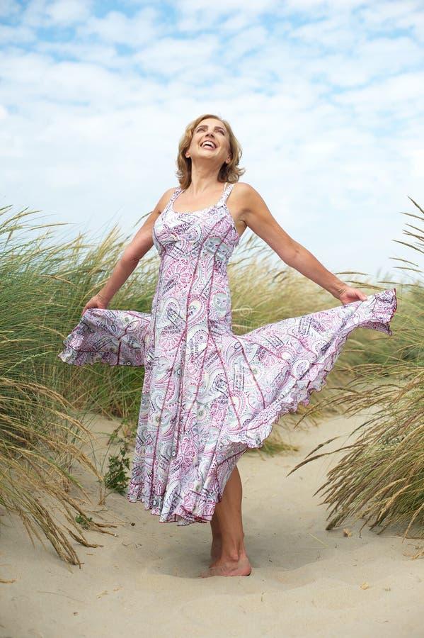 Onbezorgde oudere vrouw die bij het strand dansen royalty-vrije stock foto's