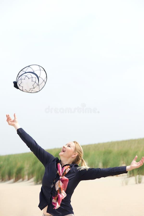 Onbezorgde oudere vrouw die hoed omhoog met uitgestrekte wapens werpen stock fotografie