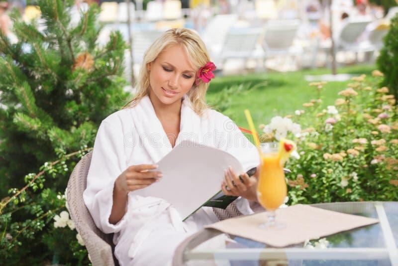 Onbezorgde schoonheid. Aantrekkelijke jonge vrouwen in badjas lezen stock foto