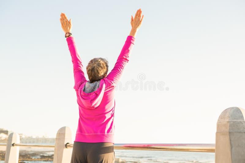 Onbezorgde sportieve vrouw met uitgestrekte wapens royalty-vrije stock foto