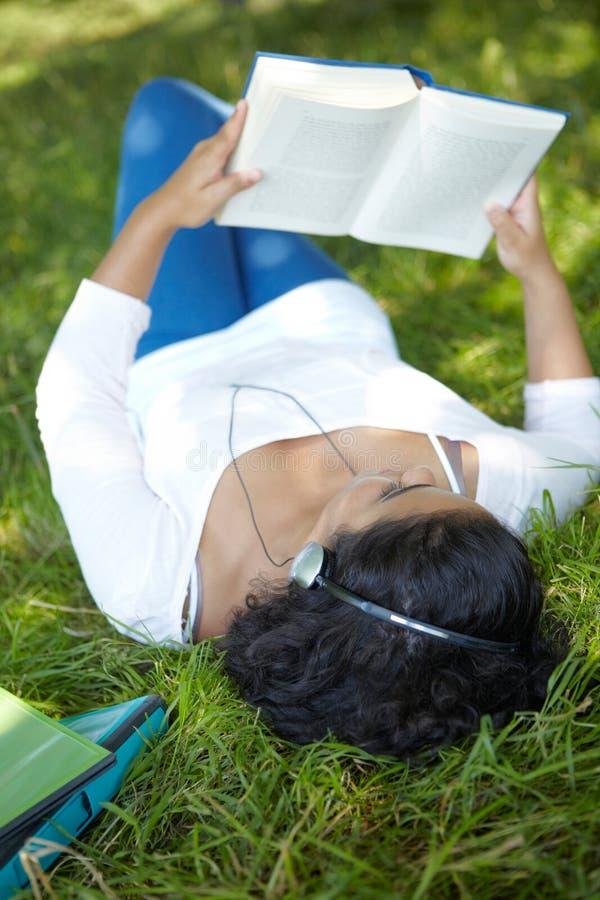 Onbezorgde Student Revising And Listening aan Muziek in Park royalty-vrije stock afbeelding