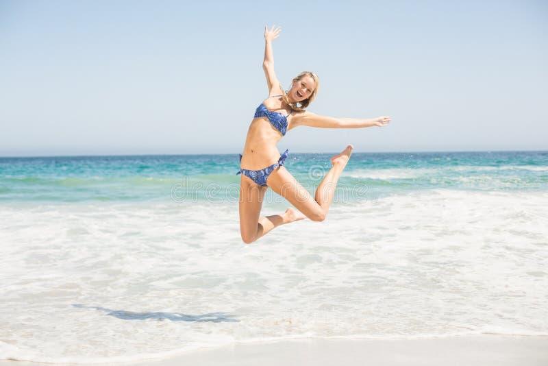 Onbezorgde vrouw die in bikini op het strand springen stock foto