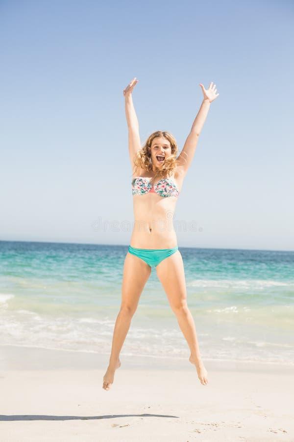 Onbezorgde vrouw die in bikini op het strand springen stock fotografie