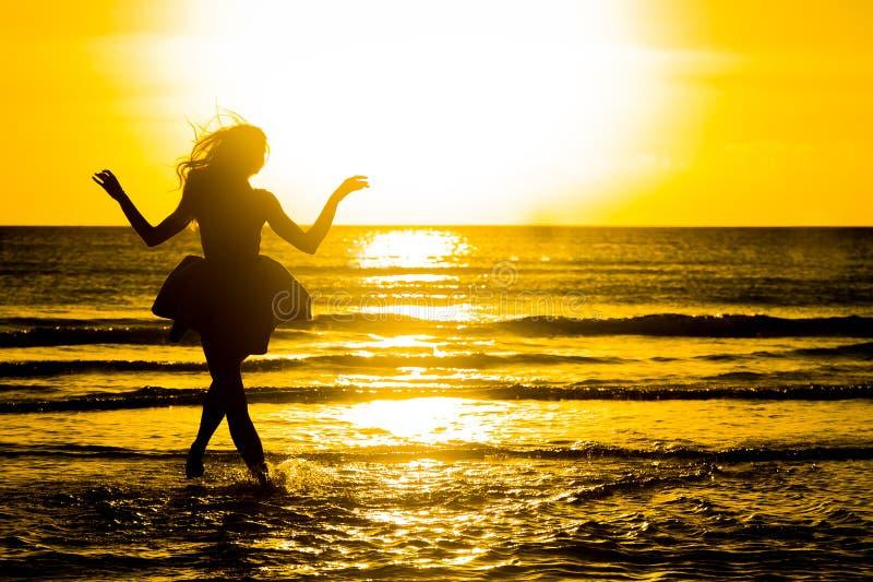 Onbezorgde vrouw die in de zonsondergang op het strand danst vakantie vitaliteit gezond het leven concept vakantievita stock fotografie
