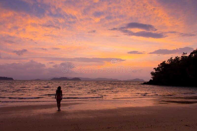 Onbezorgde vrouw die in de zonsondergang op het strand danst vakantie vitaliteit gezond het leven concept vakantievitaliteit gezo royalty-vrije stock fotografie