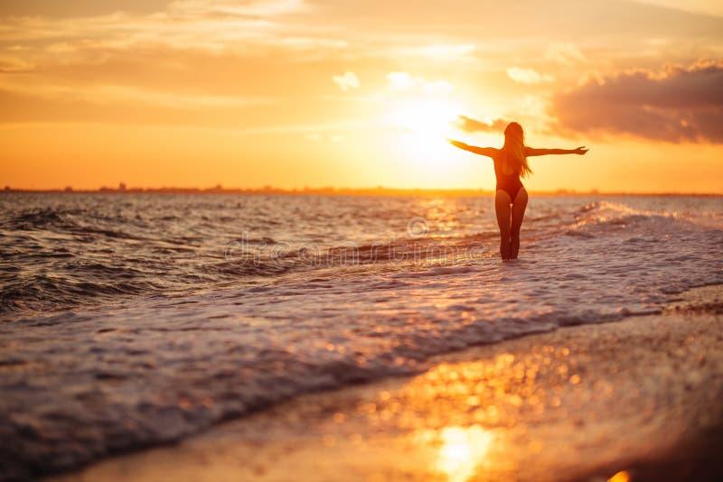 Onbezorgde vrouw die in de zonsondergang op het strand danst vakantie vitaliteit gezond het leven concept stock afbeelding