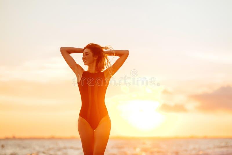 Onbezorgde vrouw die in de zonsondergang op het strand danst vakantie vitaliteit gezond het leven concept royalty-vrije stock afbeeldingen
