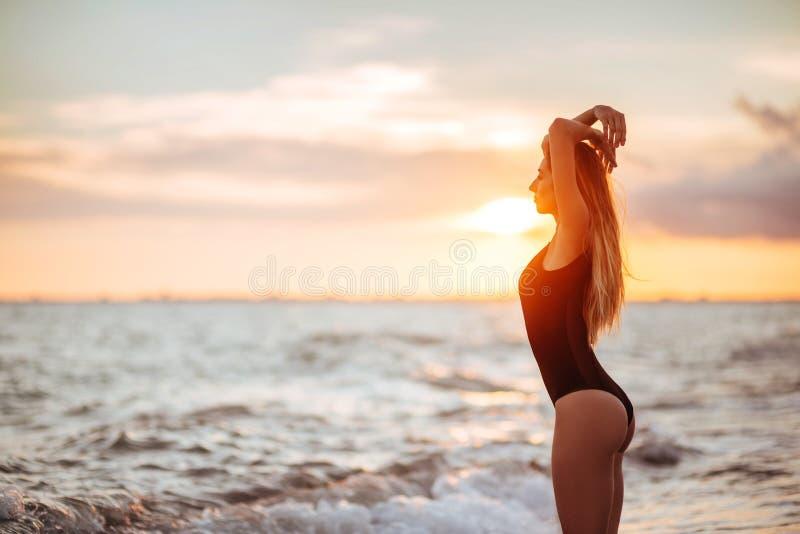 Onbezorgde vrouw die in de zonsondergang op het strand danst vakantie vitaliteit gezond het leven concept royalty-vrije stock foto