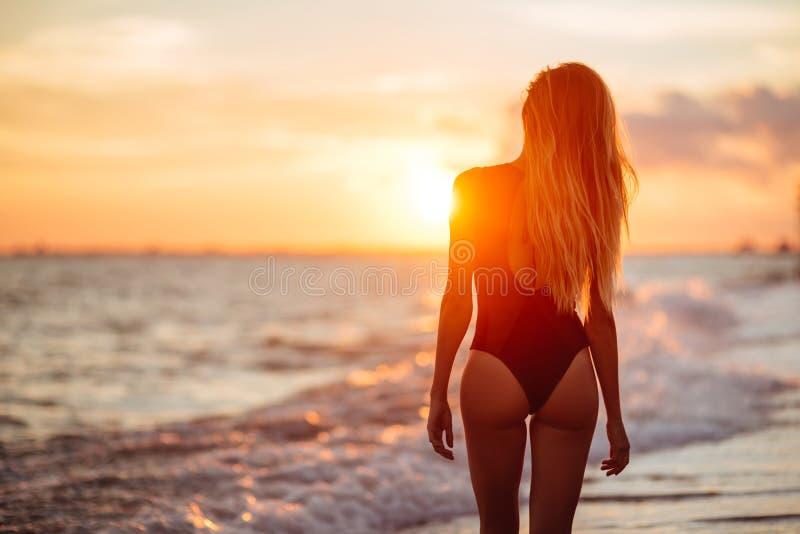 Onbezorgde vrouw die in de zonsondergang op het strand danst vakantie vitaliteit gezond het leven concept stock fotografie