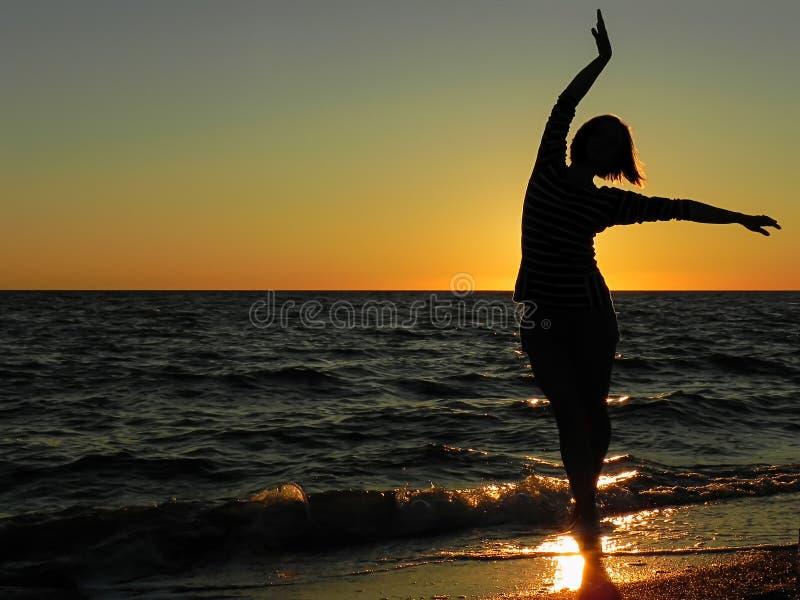 Onbezorgde vrouw die in de zonsondergang op het strand danst vakantie vitaliteit gezond het leven concept stock afbeeldingen