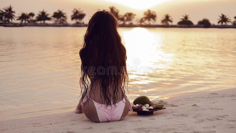 Onbezorgde vrouw die van Mooie Zonsondergang op Tropisch Strand geniet De exotische achtergrond van de Maldiven royalty-vrije stock fotografie