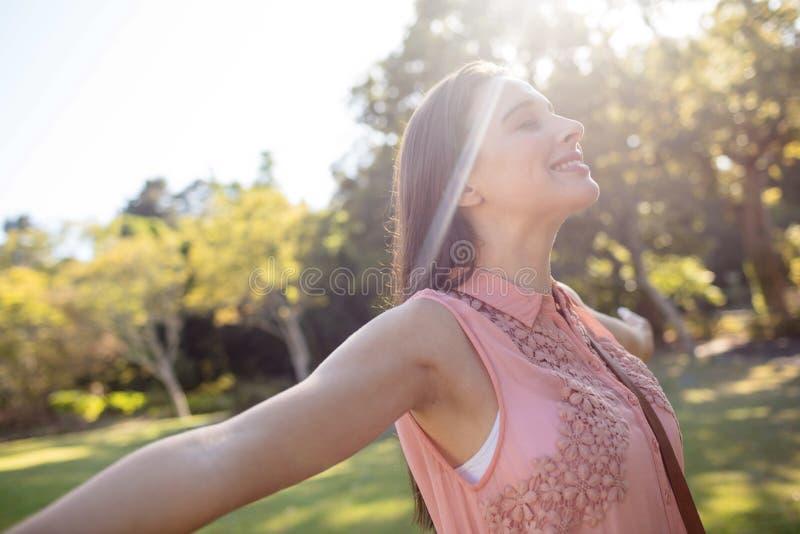 Onbezorgde vrouw die zich met haar die wapens bevinden in het park worden uitgespreid stock fotografie