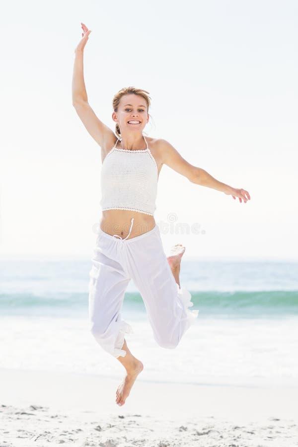 Onbezorgde vrouw in het springen op het strand stock foto's