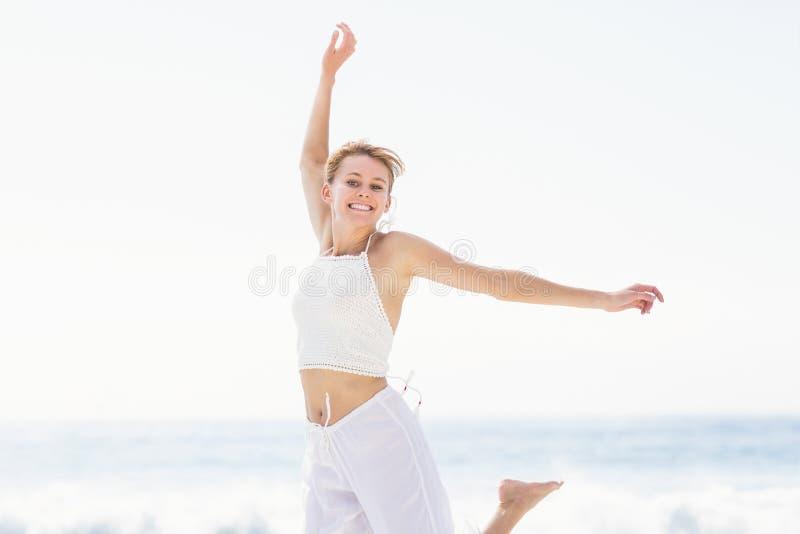 Onbezorgde vrouw in het springen op het strand stock afbeelding