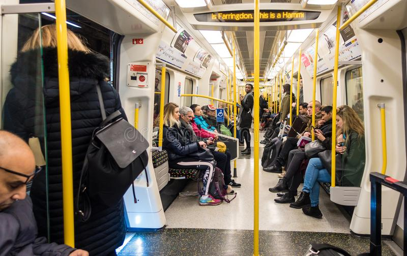 Onboard a Hammersmith and City Line train on The London Underground. Inside a carriage, passengers either sit or stand, holding onto one of the many handrails stock photos
