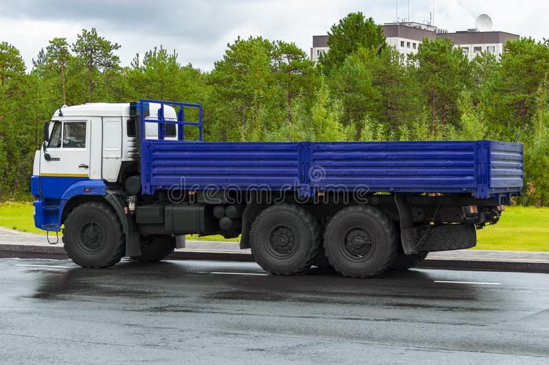 An onboard lorry with an elongated blue body and  white cab stands on  road in city in Siberia. Side view. royalty free stock photo