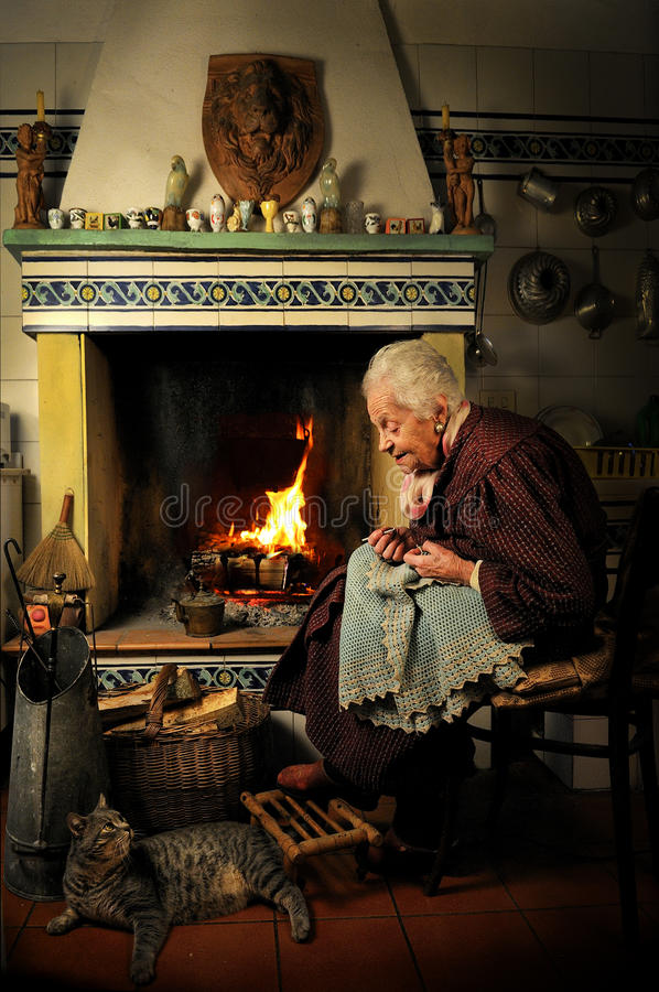 Once upon a time... An old lady relaxing with her cat in front of the fireplace stock image