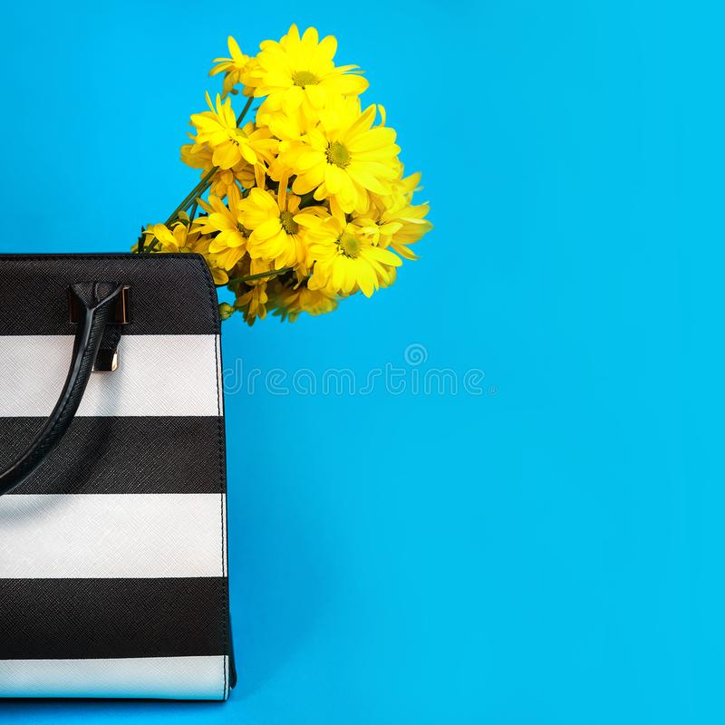 Oncept ¡ Ð подарка для бизнес-леди: цветки женской сумки аксессуаров дела черно-белой желтые на голубой предпосылке стоковое фото