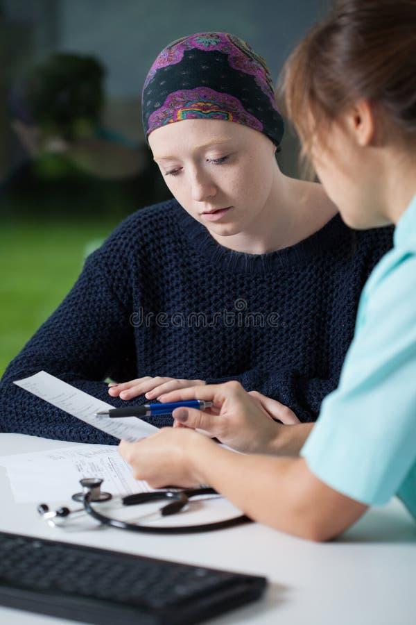 Oncologist som talar med den unga kvinnan royaltyfria foton
