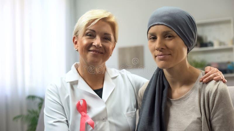 Oncologista e paciente que sofre de c?ncer que olham na c?mera, esperando para a sobreviv?ncia cura fotografia de stock