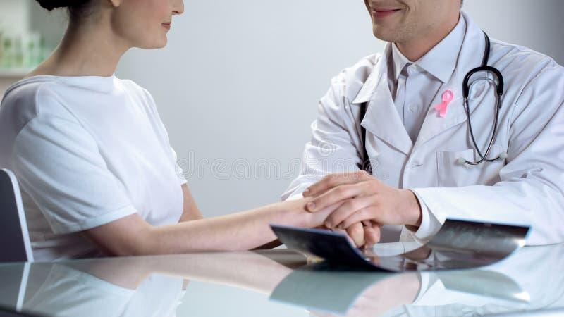 Oncologiste disant à jeune dame les bonnes actualités, aucune menace de cancer du sein chacun des deux souriant images libres de droits