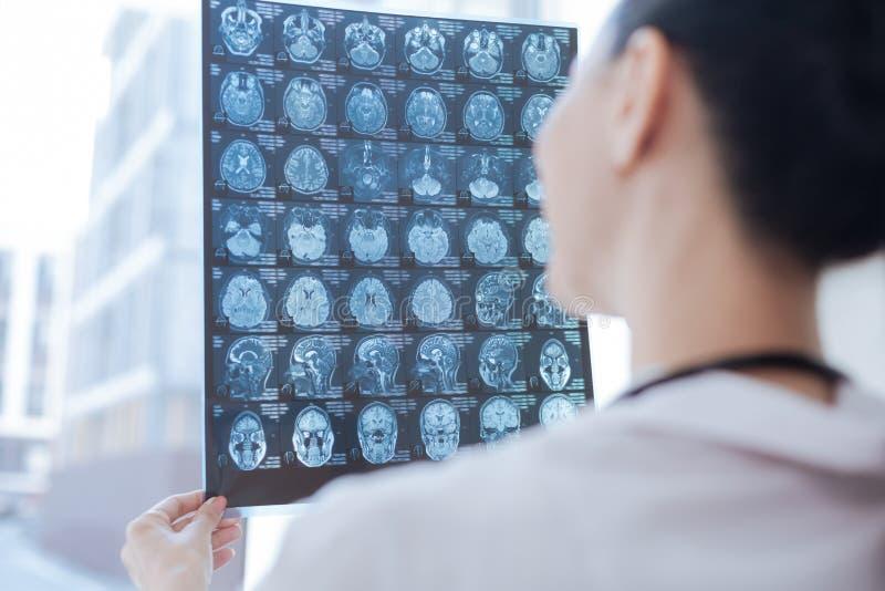 Oncologiste expérimenté examinant l'image de rayon de x à la salle roentgen photo stock