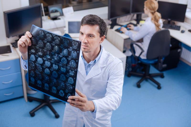 Oncologiste expérimenté sérieux examinant une image de rayon de X photos stock