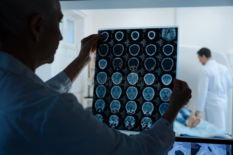 Oncologiste intelligent expérimenté regardant les résultats de balayage d'IRM photo stock